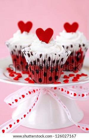 Red velvet cupcakes with cream cheese frosting decorated with red chocolate hearts