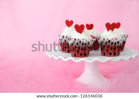 Red velvet cupcakes with cream cheese frosting decorated with red chocolate hearts. Copy space on the side.