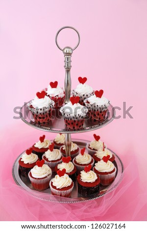 Red velvet cupcakes with cream cheese on a two tier cake stand - stock photo