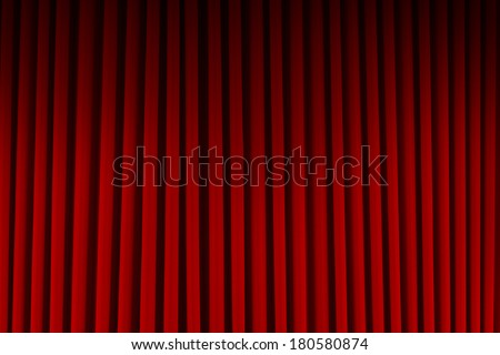 Red Velvet Stage Curtains Dim Lit Background. - stock photo