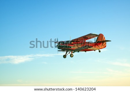 Red vintage airplane flying - stock photo