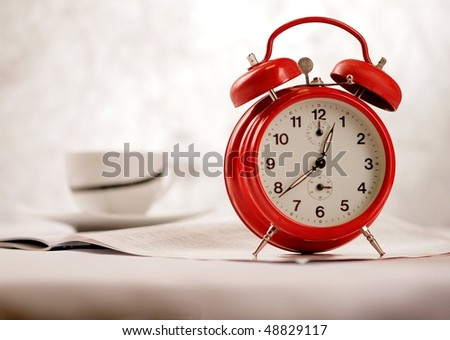Red vintage alarm clock on a table