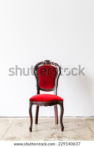 Red vintage armchair on white wall.