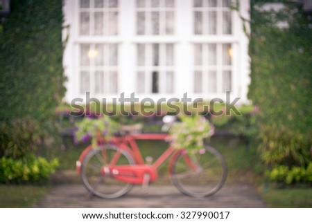 Red vintage bicycle with a flowers in a basket, Blur image for background.