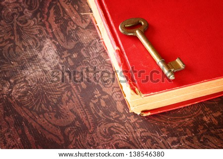 red vintage book with golden classic key on cover - stock photo