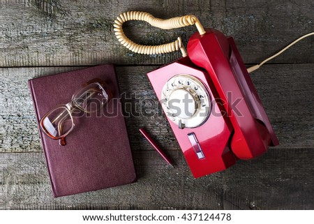 Red vintage phone, old glasses, notebook, and pencil on wooden background   close-up, top view, pick up the phone - stock photo
