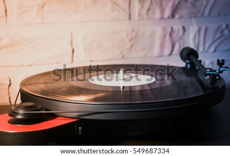 Red vintage record player with vinyl disc, close-up.