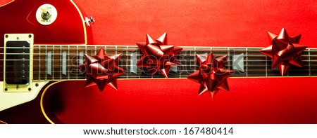 Red vintage solid body electric guitar with red ribbon bows on fretboard. A concept image for Christmas and holiday season music event.  - stock photo