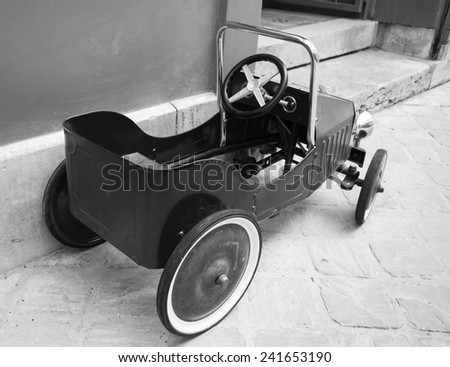 Red vintage toy car near entrance to the house. Back and side view. Aged photo. Black and white. - stock photo
