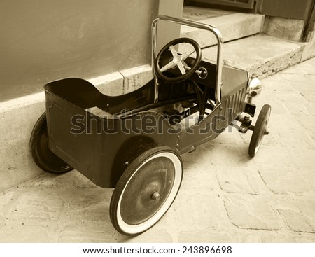 Red vintage toy car near entrance to the house. Back and side view. Aged photo. Sepia. - stock photo