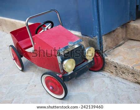 Red vintage toy car near entrance to the house. Front and side view. - stock photo
