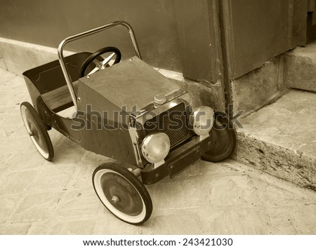 Red vintage toy car near entrance to the house. Front and side view. Aged photo. Sepia. - stock photo