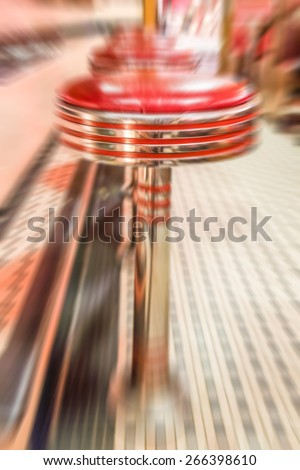 Red vinyl stools in a vintage diner. Motion blurred effect - stock photo