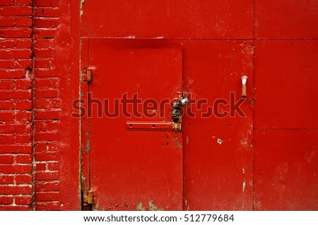 Red wall of garage with metal door closed by chain and lock