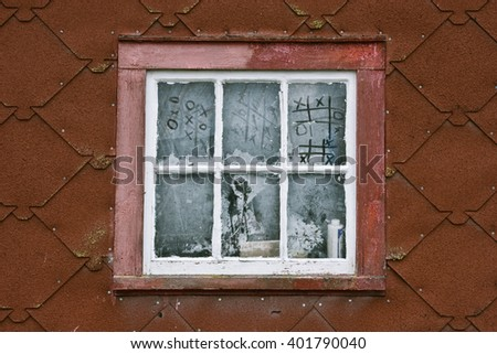 Red Wall with Dusty Window and Tic Tac Toe Written into Dust. - stock photo