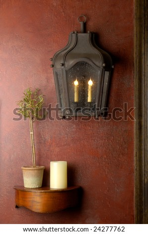 Red wall with lantern and small wooden shelf. - stock photo