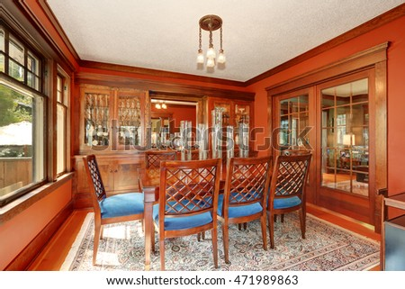 Red walls in dining room. Burgundy wooden table and carved chairs with blue seats. Northwest, USA