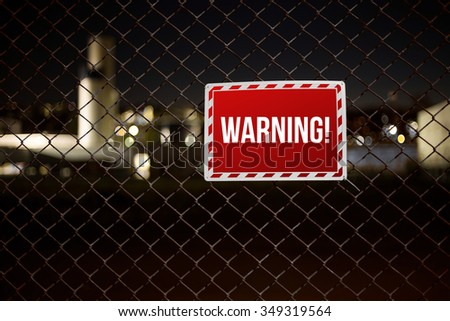 Red Warning sign on private property hanging on a chainlink fence during night - stock photo