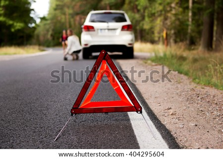 Red warning triangle and broken car in the middle of forrest - stock photo