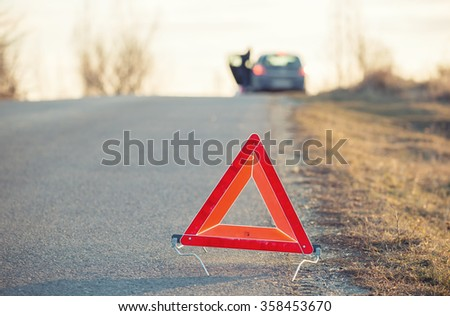 Red warning triangle on a road with a broken down car in the background in sunset light - stock photo