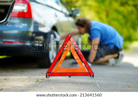 Red warning triangle sign on the road with a man checking his broken car in background - stock photo