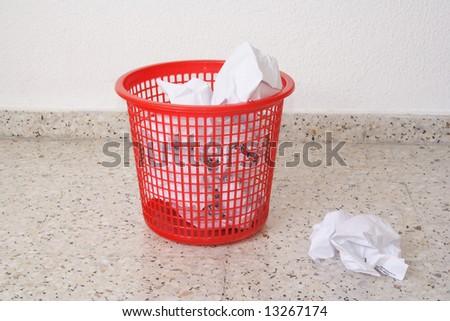 Red waste basket on the granite floor - stock photo
