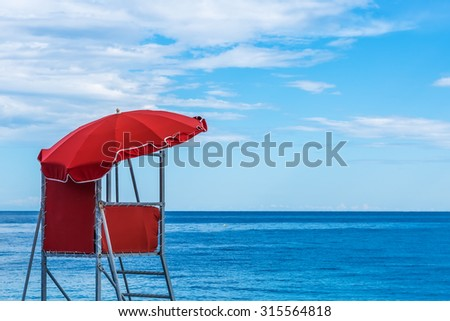 Red watch tower overlooking the beach, against the blue ocean and sky  - stock photo