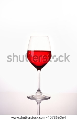 Red water in wine glass on white background