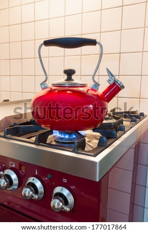 Red water kettle heating up on the stove - stock photo