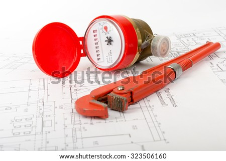 Red water meter with wrench on draft background