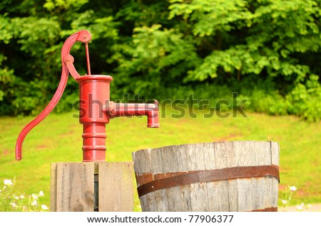 red water pump in field - stock photo