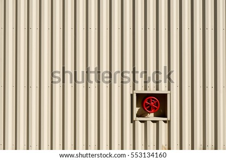 Red Water Valve on Striped Metal Building
