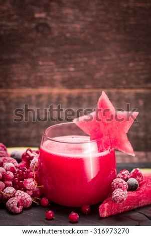 Red watermelon and berries smoothie on wooden vintage background,healthy detox drink.