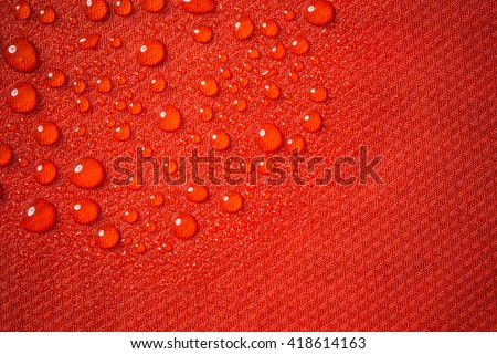 Red waterproof fabric close up with water beads