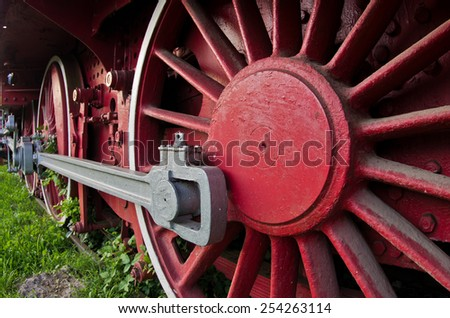 Red wheels of big old steam locomotive from Orient Express, in front of a factory where it has been produced - stock photo