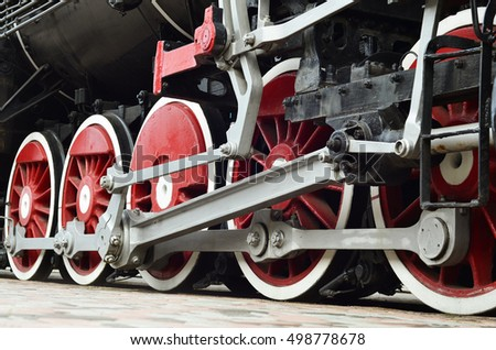 Red wheels of old USSR black steam locomotive