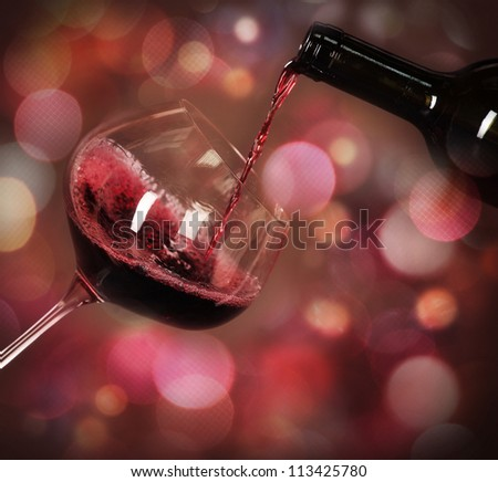 Red whine being poured in the wine cellar - stock photo