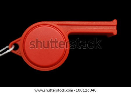 Red whistle isolated on black - stock photo