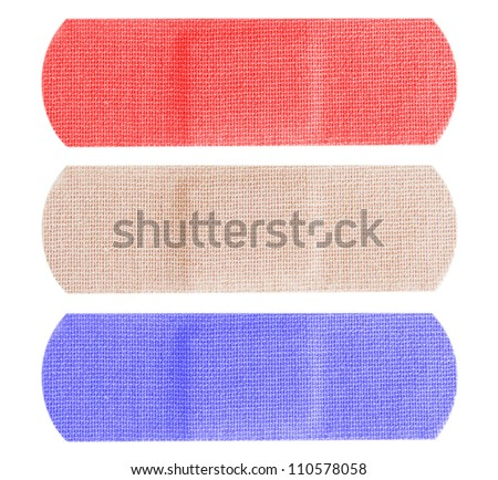 Red, white and blue bandages or bandaids isolated on white background. - stock photo
