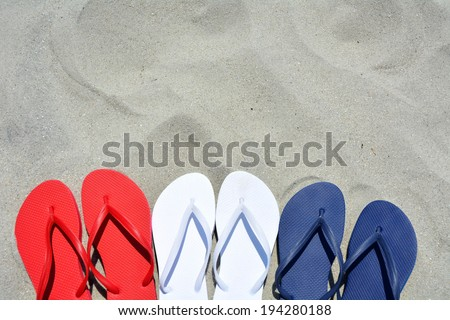 Red white and blue flip flops on the sand. Plenty of room for your text - stock photo