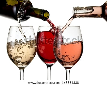 Red, white and rose wine pouring in three glasses from bottles - stock photo