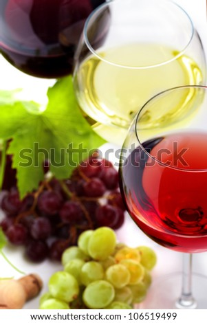 Red, white and rose wine with grapes and leaves over white background with copy space.