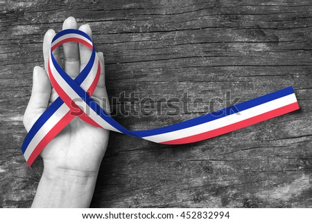 Red white blue color flag pattern ribbon on human hand on old aged background (clipping path) Symbolic icon for national support, Patriotism, remembrance or mourning for tragic incident - stock photo