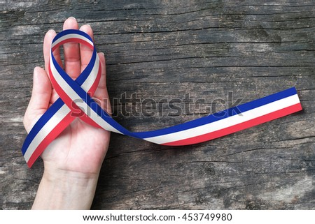 Red white blue flag pattern ribbon on human hand on old aged background (clipping path) Symbolic icon for national support - stock photo