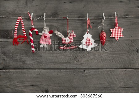 Red white checked christmas decoration hanging on an old wooden wall background. - stock photo