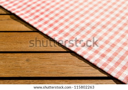 Red white checkered table cloth on a wooden table