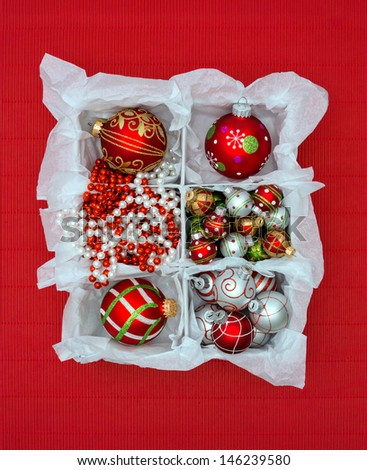 Red & white Christmas ornaments in a box on textured red background.  - stock photo