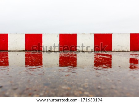 Red white concrete wall on the wet asphalt - stock photo