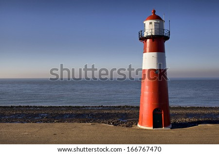 Red-white lighthouse on the coast of North Sea at Westkapelle, Netherlands - stock photo