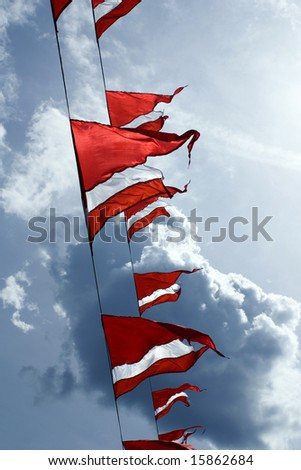 Red-white triangular ship flags flap in the breeze against a cloudy sky - stock photo